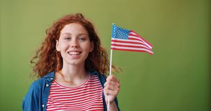 Attractive redhead teenager holding American flag on green background. Attractive redhead teenager is holding national American flag on green background smiling stock video footage