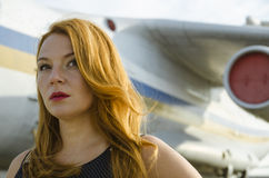 Attractive redhead woman about aircraft outside to travel Royalty Free Stock Image
