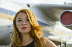 Attractive redhead woman about aircraft outside to travel Royalty Free Stock Photo