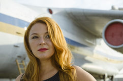 Attractive redhead woman about aircraft outside to travel Stock Photo