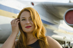 Attractive redhead woman about aircraft outside to travel Royalty Free Stock Photos