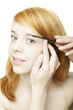 Attractive redhead woman applying mascara Royalty Free Stock Photography