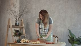 Lovely woman making edible bouquet at workshop. Attractive redhead woman in apron collecting cheese and wine edible bouquet at workplace. Concentrated female stock footage