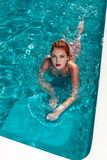 Attractive redhead woman laying in pool Royalty Free Stock Image