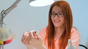 Attractive redhead woman looks at her new manicure and smile royalty free stock image