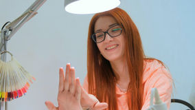 Attractive redhead woman looks at her new manicure and smile Stock Photo