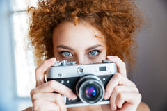 Attractive redhead woman photographer using old camera Stock Images