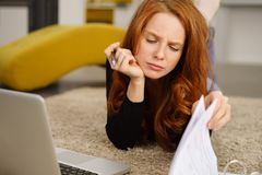 Attractive redhead woman studying or working stock photography