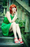 Attractive redheaded girl. An attractive redheaded girl sits on a background an age-old stair Stock Image