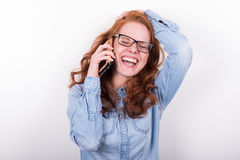 Attractive redheaded woman is laughing during a phone call.  Royalty Free Stock Image