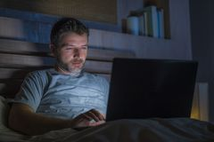 Attractive and relaxed internet addict man networking concentrated late at night on bed with laptop computer in social media. Young aroused man alone in bed royalty free stock photos