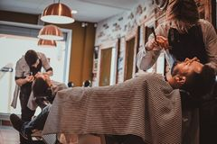Thendy hairdresser at modern barbershop is working on client`s haircut. Attractive relaxed men just got great service from talanted trendy barber royalty free stock photo