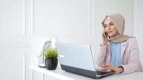 Attractive relaxed muslim woman is talking mobile phone sitting on her workplace. Portrait of attractive relaxed smiling muslim woman in hijab and suit is stock footage