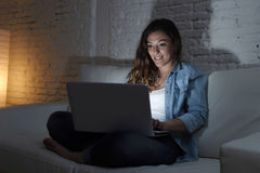 Attractive relaxed woman at home sitting happy on couch using laptop at night Stock Photography