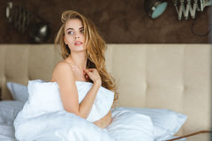 Attractive relaxed young woman sitting on bed. Attractive relaxed young woman wrapped in white duvet sitting on bed Stock Image