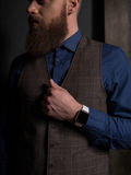 Attractive rich man with a big beard. Successful young businessman is waiting for someone. He is standing and touching his clothing nervously. The bearded guy stock photos