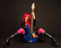 Attractive rock girl sitting with bass guitar Royalty Free Stock Photography