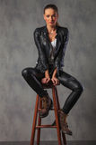 Attractive rocker woman in leather posing seated in studio Stock Image