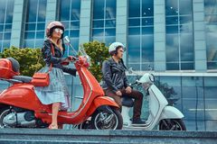 Attractive romantic couple, a handsome man and female, sitting on retro Italian scooters against a skyscraper. royalty free stock images