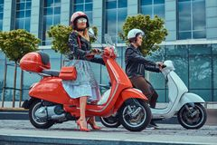 Attractive romantic couple, a handsome man and female, sitting on retro Italian scooters against a skyscraper. royalty free stock photos
