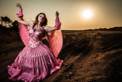 Attractive romantic woman on beautiful pink dress pose outdoor. Royalty Free Stock Image
