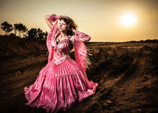 Attractive romantic woman on beautiful pink dress pose outdoor. Royalty Free Stock Photo