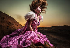 Attractive romantic woman on beautiful pink dress pose outdoor. Stock Photos