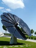 Attractive rotating and turning flower shaped solar panel. Attractive rotating and turning intelligent self adjusting flower shaped solar panel in rural setting royalty free stock image
