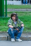 Attractive Russian teenager wearing headphones and sitting on the road. royalty free stock image