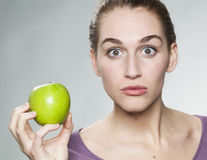 Attractive 20s girl amazed by the artificial look of a fruit Royalty Free Stock Images