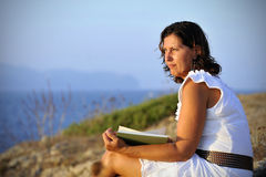 Attractive 40s mature woman reading and looking at horizon pensive. Attractive 40s woman sitting alone on the beach sitting in front of the sea reading a book Royalty Free Stock Image