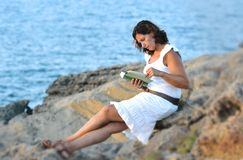 Attractive 40s mature woman reading and looking at horizon pensive. Attractive 40s woman sitting alone on the beach sitting in front of the sea reading a book Stock Photo