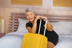 Attractive 40s to 50s mature Asian tourist woman with grey hair arriving in hotel room excited smiling  cheerful enjoying business. Happy and attractive 40s to royalty free stock photo