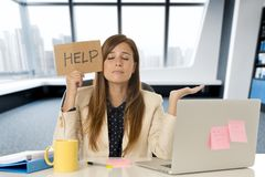 Attractive sad and desperate business woman suffering stress at office laptop computer desk holding help sign Stock Images