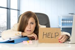 Attractive sad and desperate business woman suffering stress at office laptop computer desk holding help sign royalty free stock images