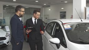 Sales manager explaines the contract to the customer at the car dealership stock photos