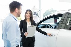 Would You Like To Test Drive Before Buying. Attractive sales worker opening car door for mid adult client in showroom stock image