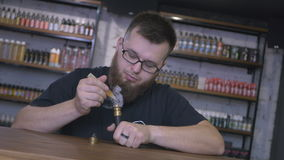 Attractive salesman with beard fill the electronic cigarette with liquid stock video footage