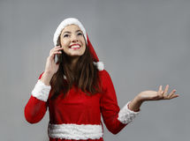Attractive santa  claus  girl smiling and make call. With  cell phone Royalty Free Stock Photography
