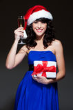 Attractive santa girl with glass and gift Stock Photo