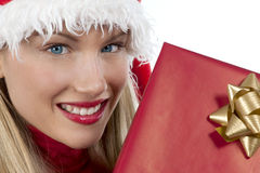 Attractive Santa girl with present. Rich, colorful series of attractive young woman in santa's hat with presents Royalty Free Stock Photo
