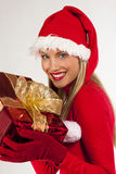 Attractive Santa girl with present. Rich, colorful series of attractive young woman in santa's hat with presents Stock Image