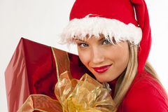 Attractive Santa girl with present. Rich, colorful series of attractive young woman in santa's hat with presents Royalty Free Stock Image