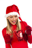 Attractive Santa girl surprising while receiving a. Rich, colorful series of attractive young woman in santa's hat with presents Stock Photography