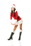 Attractive santa woman standing astride and inclined, looking to the camera Stock Images