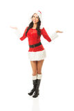 Attractive santa woman standing, holding something invisible in both hands.  royalty free stock images