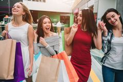Attractive and satisfied girls are walking in mall together. They are holding bags with stuff. Girls are laughing and. Having some fun royalty free stock images