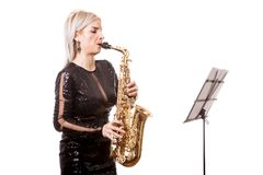 Attractive saxophonist woman playing at her musical instrument Royalty Free Stock Images