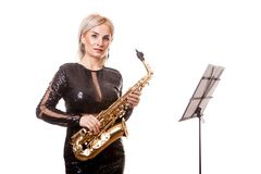 Attractive saxophonist woman playing at her musical instrument Stock Photo