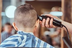 Attractive school boy is getting trendy haircut from mature hairdresser at fashionable hairdressing salon.  stock photos
